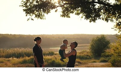 Young family with baby on sunset
