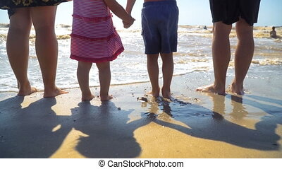Young family with children are standing on the beach holding hands and looking at the sea