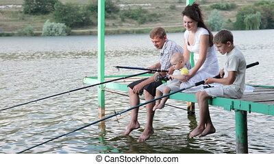Young family with children spending weekend fishing by the lake