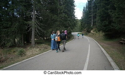 Young family with children walking along country road in autumn afternoon.