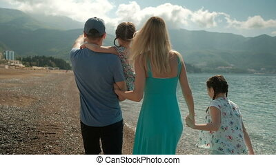 Young family with children walking along shore on summer day.