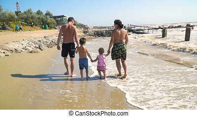 young family with children walking along the sandy beach and holding hands