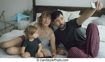 Young family with cute little girl taking selfie portrait on smartphone camera sitting in bed at home