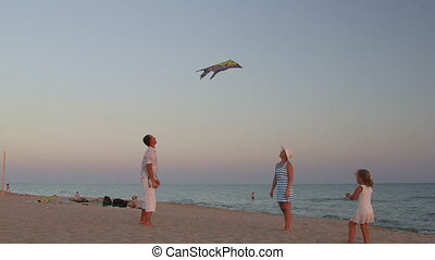 Young family with daughter flying colourful kite in the sky on sandy beach