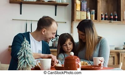 Young family with daughter on the kitchen