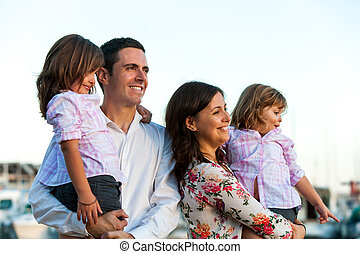 Young family with daughters at sunset.