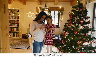 Young family with daugter at Christmas tree at home.