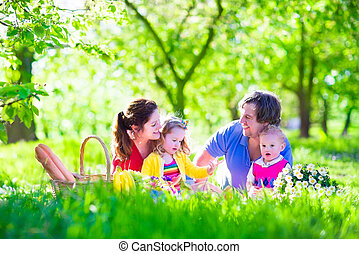 Young family with kids having picnic outdoors. Parents with...