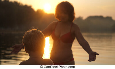 Young family with little child having enjoyable time at the sea during beautiful sunset happy vacation time.