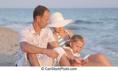 Young family with little daughter sitting in evening on sand beach