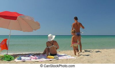 Young family with little daughter on sand beach flying colourful kite in the sky