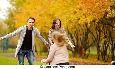 Young family with little kids in autumn park on sunny day