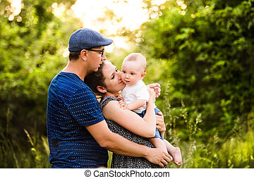 Young family with little son in sunny summer nature
