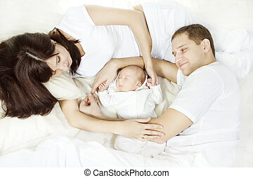 Young family with newborn baby lying down and looking at...