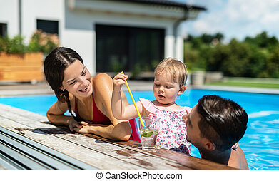 Young family with small daughter in swimming pool outdoors in backyard garden.