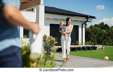 Young family with small daughter outdoors in backyard garden, relaxing.