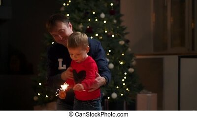 Young family with sparklers at Christmas time at home