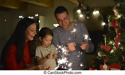 Young family with sparklers at Christmas tree at home. -...