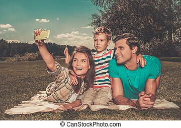 Young family with their child making selfie on a blanket outdoors