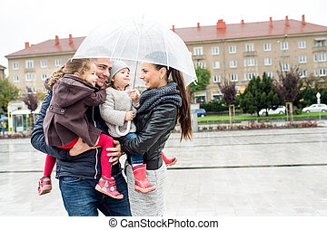 Young family with two daughters under the umbrella, town