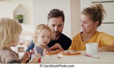 Young family with two small children indoors in bedroom playing with toys.