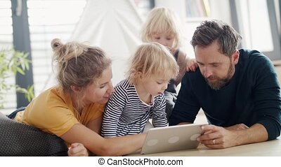 Young family with two small children indoors in bedroom, using tablet.