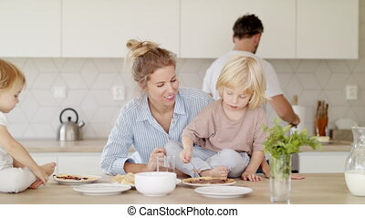 Young family with two small children indoors in kitchen, making pancakes.
