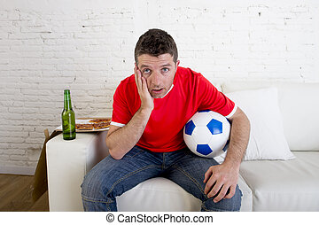 young fan man watching football game on television wearing team jersey suffering nervous and stress