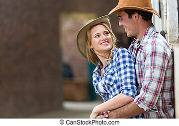 young farm couple embracing