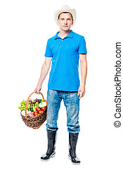 Young farmer portrait with a basket of vegetables on a white background in full length