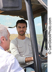 Young farmer talking to older man