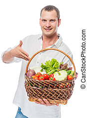 Young farmer with vegetables in a basket shows crop on white background