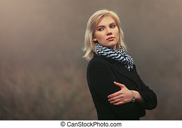 Young fashion blond woman in black coat walking in a fog outdoor