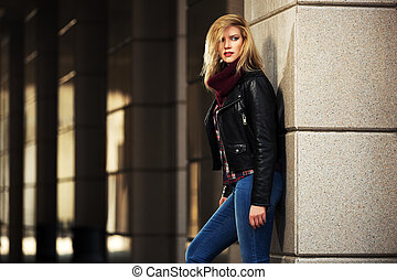 Young fashion blond woman in leather jacket at the wall