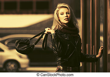 Young fashion blond woman in leather jacket with handbag