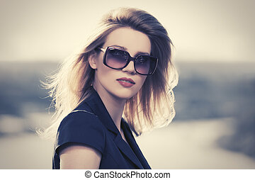 Young fashion blond woman in sunglasses outdoor
