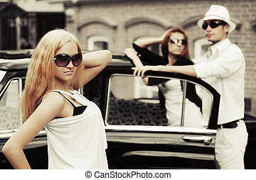 Young fashion blond woman next to retro car