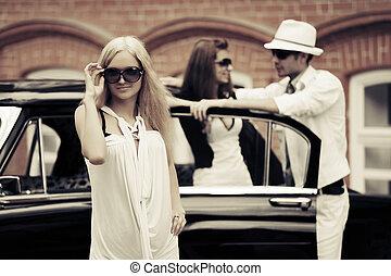 Young fashion blonde woman next to retro car