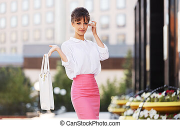 Young fashion business woman in white blouse and pencil skirt walking in city street