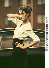 Young fashion business woman in white shirt and pencil skirt next to her car