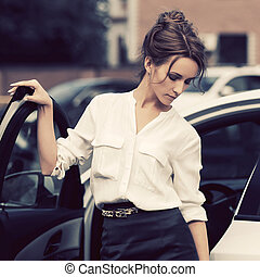Young fashion business woman in white shirt and pencil skirt outside her car