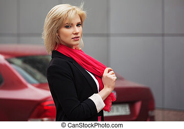 Young fashion business woman next to her car