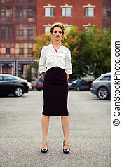 Young fashion business woman standing on the car parking