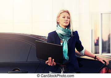Young fashion business woman with laptop next to her car
