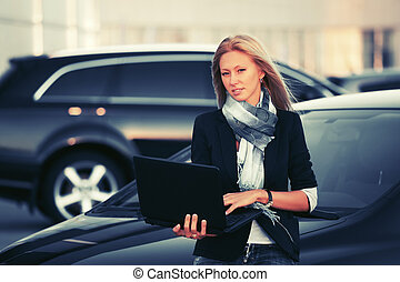 Young fashion business woman with laptop standing next to her car