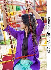 young fashion caucasian brunette woman portrait sit on flying carousel in amusement park summer