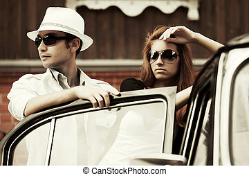 Young fashion couple at the car