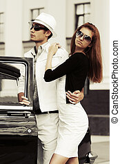 Young fashion couple by retro car