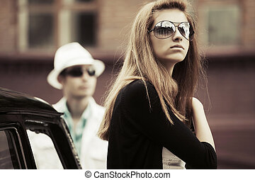 Young fashion couple in conflict at the retro car