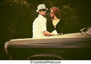 Young fashion couple in love next to vintage car